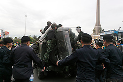 © Licensed to London News Pictures. 28/05/2014. Thai Army jump onto the back of an Army Humvee and evacuate after being pelted with projectiles from Anti-Coup protestors during a Anti-Coup protest at Victory Monument Bangkok Thailand.  Photo credit : Asanka Brendon Ratnayake/LNP