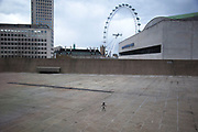 Tiny metal figure by David Shrigley stands on the rooftop of the Hayward Gallery in London with a view of the London Eye. Shrigley was born on 17 September 1968. Although he works in various media like this sculpture, he is best known for his mordantly humorous cartoons released in various forms. UK.