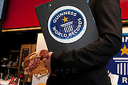 An official from the Guinness book of records hold a clip board before Nico Jimenez from Spain, breaks the world record for the longest slice of meat with an Iberico Ham from sposor, Iberselec, that he sliced to a length of 13 metres, 35 centimetres. This broke his own world record, set in 2008, by three centimetres. Hattori school of nutrition, Yoyogi, Tokyo, Japan. September 23rd 2010