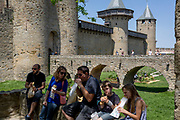 A family of children and parents eat lunch in front of medieval towers, on 27th May, 2017, in Carcasonne, Languedoc-Rousillon, south of France. Situated on the right bank of the Aude, the City, a medieval village that is still inhabited, has 52 towers and two concentric walls totalling 3 km in length.