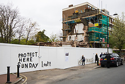 Maida Vale, London, April 26th 2015. Dozens of local residents and regulars gather outside the much loved, partially demolished Carlton Tavern in Maida Vale to protest against its sudden, illegal demolition by property developers. They demand that the pub, rebuilt in 1920 following a World War One zeppelin bombing is once again rebuilt brick-by-brick, saying that any fines levied by the council will have een factored into the development budget.  PICTURED: Scrawled on the hoarding surrounding the partially demolished Carlton Tavern is a notice of the protest.
