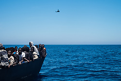MEDITERRANEAN SEA, LIBYA - JUNE 15 :  A Libyan helicopter over as refugees wait to get on onboard the rescue vessel Golfo Azzurro by members of the Spanish NGO Proactiva Open Arms, after being rescued from a wooden boat sailing out of control in the Mediterranean Sea near Libya on Thursday, June 15, 2017. A Spanish aid organization Thursday rescued 420 migrants who were attempting the perilous crossing of the Mediterranean Sea to Europe in packed boats from Libya. Marcus Drinkwater / Anadolu Agency  | BRAA20170615_365 Mediterranean Sea Libye Libya