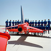 In the mid-day heat, all members of the elite 'Red Arrows', Britain's prestigious Royal Air Force aerobatic team, stand on the wings of a Hawk aircraft as the official photograph is taken on PDA Day at RAF Akrotiri, Cyprus. PDA (or 'Public Display Authority'), is when they are allowed by senior RAF officers to perform as a military aerobatic show in front of the public - following a special test flight when their every move and mistake is assessed and graded. Until that day arrives, their training and practicing is done in the privacy of their own airfield at RAF Scampton in Lincolnshire, UK or here in the glare of Akrotiri. The pilots are called reds and their ground crew, the Blues after their summer air show uniforms. Since 1965 the team has flown over 4,000 air shows in 52 countries.