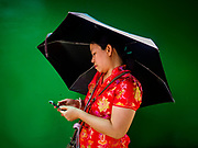16 FEBRUARY 2018 - BANGKOK, THAILAND: A woman uses her umbrella for shade while she checks her smart phone at Wat Mangkon Kamalawat during Chinese New Year celebrations in the Chinatown neighborhood of Bangkok. Thailand has a large Chinese community and Lunar New Year is widely celebrated, especially in larger cities. This will be the Year of the Dog.       PHOTO BY JACK KURTZ