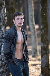 man with an open button down sweater leaning against a tree