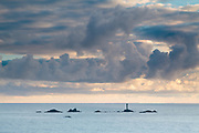 Stormy skies over Longships lighthouse, Land's End. The Isles of Scilly are just visible on the horizon. Cornwall, England, UK