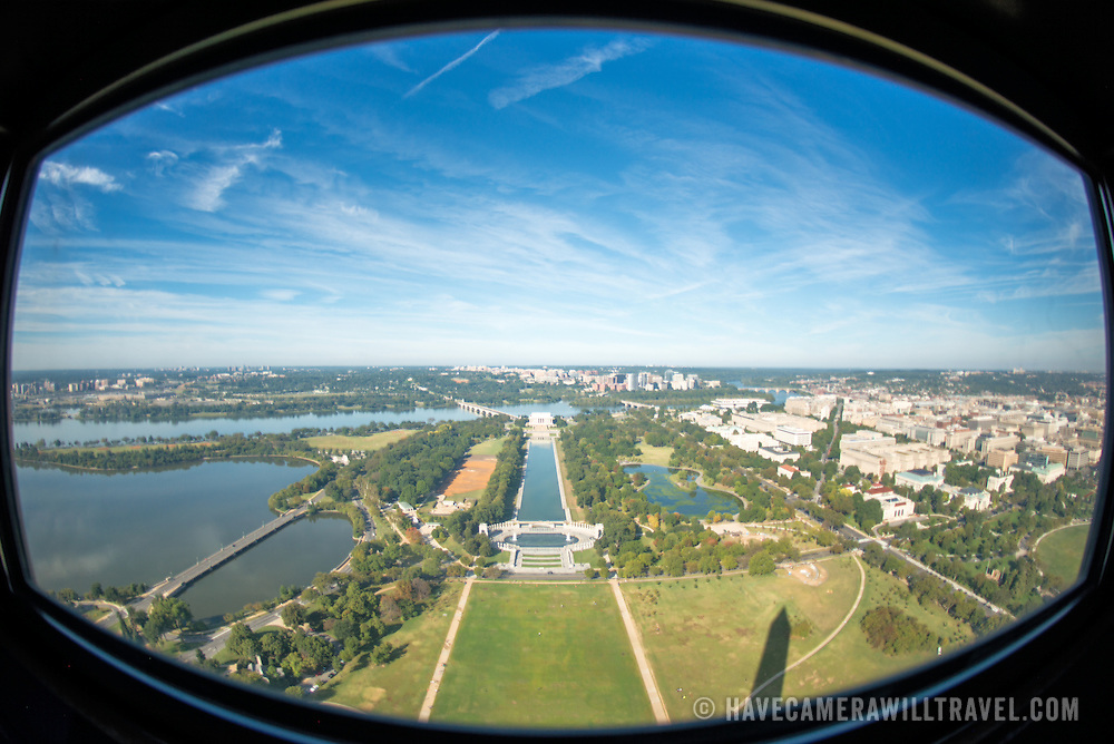 The view from one of the windows at the top of the Washington Monument, looking out over the Reflecting Pool and the Lincoln Memorial towards Arlington Memorial Bridge and Arlington, VA. The Washington Monument stands at over 555 feet (169 metres) at the center of the National Mall in Washington DC. It was completed in 1884 and underwent extensive renovations in 2012-13 after an earthquake damaged some of the structure.