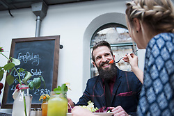 Woman feeding food to man at restaurant