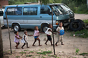Children play just outside Marble Moahi's fence in Kabakae Village, Ghanzi, Botswana.  (Marble Moahi is featured in the book What I Eat: Around the World in 80 Diets.) .