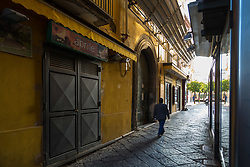 Sorrento, Italy, September 13 2017. A man walks towards the bright morning sunshine, photographed on an early morning walkabout in Sorrento, Italy. © Paul Davey