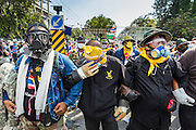 01 DECEMBER 2013 - BANGKOK, THAILAND: Thai anti-government protestors wearing gas masks and breathing filters confront riot police in Bangkok. Thousands of anti-government Thais confronted riot police at Phanitchayakan Intersection, where Rama V and Phitsanoluk Roads intersect, next to Government House (the office of the Prime Minister). Protestors threw rocks, cherry bombs, small explosives and Molotov cocktails at police who responded with waves of tear gas and chemical dispersal weapons. At least four people were killed at a university in suburban Bangkok when gangs of pro-government and anti-government demonstrators clashed. This is the most serious political violence in Thailand since 2010.    PHOTO BY JACK KURTZ