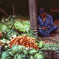 A fruit and vegetable merchant sells his wares in the Bazaar in Kathmandu, Nepal, 1977.