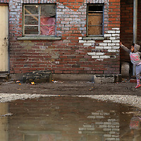 A girl dances near a puddle in the middle of Langa Township.<br /> Photo by Shmuel Thaler <br /> shmuel_thaler@yahoo.com www.shmuelthaler.com