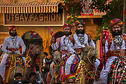 Parading on the backs of camels, Rajasthani men in traditional costumes at the Desert Festival on 29th January 2018  in Jaisalmer, Rajasthan, India. It is an annual event that take place in February month in the beautiful city Jaisalmer. It is held in the Hindu month of Magh February, three days prior to the full moon. The men flaunt their moustaches, which go well with the Rajputana spirit that symbolizes the valor and glory of Rajasthan.