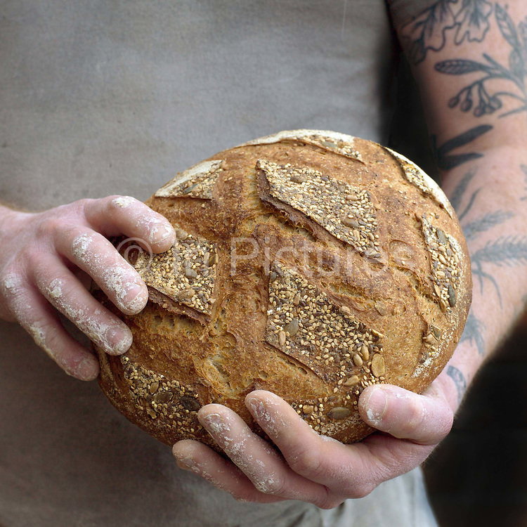 Baker Philip Clayton holding a Heritage loaf at the Haxby Bakehouse, Yorks artisan bakery in Haxby, North Yorkshire, United Kingdom on 10th February 2017. Haxby Bakehouse make bread using traditional methods of slow fermentation. They use low yeasted overnight sponges, natural sourdough levain or a combination of the two. This means the bread they produce is full of flavour without the use of any artificial flour improvers, preservatives or emulsifiers.