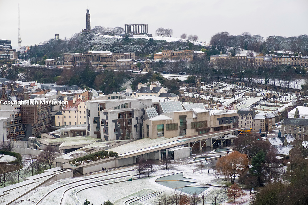 Snow falls on city of Edinburgh in December. Skyline view of city towards the Scottish Parliament Building at Holyrood and Calton Hill.