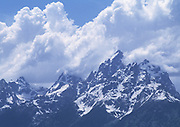 Distant view of the Grand Teton Mountains with snow and  big clouds