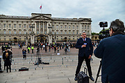A news broadcaster speaks to camera as members of the public queue to read the official notice of the birth of a baby boy to the Duke and Duchess of Sussex outside Buckingham Palace on May 6, 2019 in London,England, United Kingdom. Meghan, Duchess of Sussex gave birth to a baby boy weighing 7lbs 3oz at 05:26 BST.