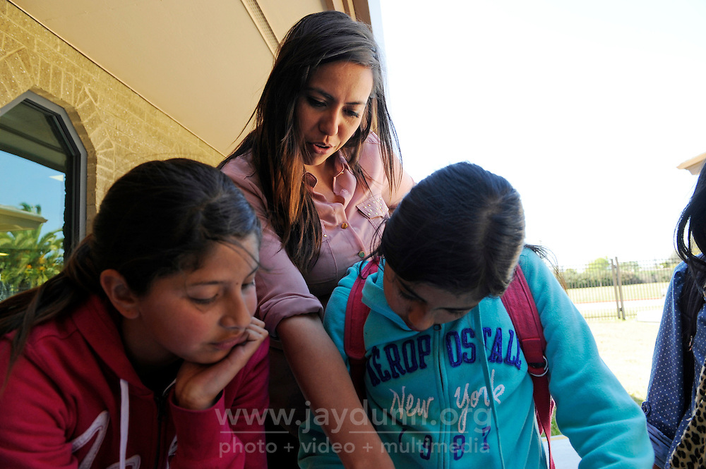 """Carissa Purnell helps kids with their homework during snack time at the Cesar Chavez Library in Salinas. Food is served as part of a supervised homework and activities program funded by a """"Building Healthy Communities"""" grant organized by Purnell, manager of technology for the library."""