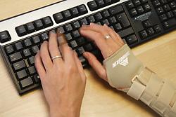 RSI sufferer wearing wrist sports support splint while using computer keyboard