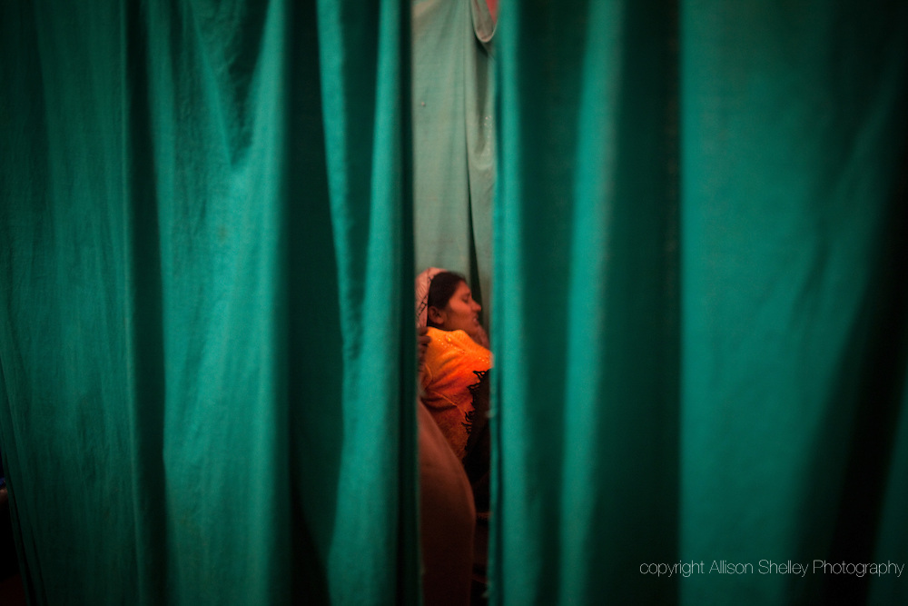 Rinu Devi, rests between contractions on a bed in the Rita Varma clinic, a private clinic in the town of Bodhgaya in the state of Bihar, India, December 8, 2011.  Her first child, a girl, was born later that night but was rushed to a hospital in the larger town of Gaya for treatment.