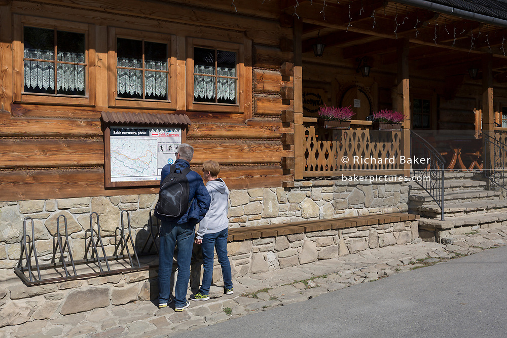 Walkers and a hiking trail map outside the Bocowka log restaurant, a traditional mountain log cabin in southern Poland, on 21st September 2019, in Jaworki, near Szczawnica, Malopolska, Poland.