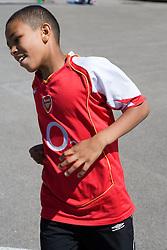 Boy taking part in running race in school playground,