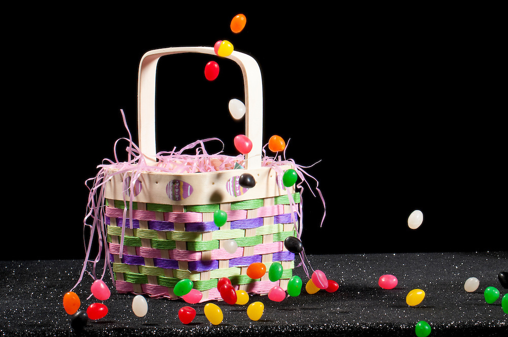 Easter basket in black background with candies falling on it.