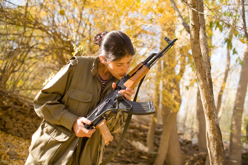 PKK member Rengin Ararat, 31, from Afrin in Syria, blows dust off from her gun in Qandil Mountains, Iraqi Kurdistan. She has been with PKK for 12 years. She is a guerrilla fighter and carries her own gun and her current duty is to work at sewing workshop.
