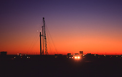 Stock photo of trucks leaving a drilling site at dusk
