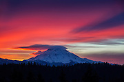 At sunrise, Mount Rainier casts its own shadow on a layer of cirrostratus clouds in this view from Bonney Lake, Washington. The mountain is also capped by a lenticular cloud. Mount Rainier, the highest peak in Washington state and the tallest volcano in the Cascade Mountain Range, has a summit elevation of 14,411 feet (4,392 meters).