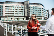 People chatting at the waterfront and marina with Castle Quay apartments in the view beyond in Jersey, CI