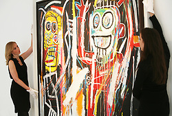 © Licensed to London News Pictures 10/04/2013.Christie's employees straighten Jean-Michel Basquiat's painting 'Dustheads', estimated between $25 - $35 million, that is on display at Christie's in central London and due to go on auction on the 15th May in New York. .London, UK.Photo credit: Anna Branthwaite