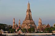 "08 MARCH 2009 -- BANGKOK, THAILAND: Sunrise on Wat Arun, a Buddhist temple (wat) in the Bangkok Yai district of Bangkok, Thailand, on the west bank of the Chao Phraya River. The full name of the temple is Wat Arunratchawararam Ratchaworamahavihara. The outstanding feature of Wat Arun is its central prang (Khmer-style tower). It may be named ""Temple of the Dawn"" because the first light of morning reflects off the surface of the temple with a pearly iridescence. Steep steps lead to the two terraces. The height is reported by different sources as between 66,80 m and 86 m. The corners are surrounded by 4 smaller satellite prangs. The prangs are decorated by seashells and bits of porcelain which had previously been used as ballast by boats coming to Bangkok from China. The central prang is topped with a seven-pronged trident, referred to by many sources as the ""trident of Shiva"". Around the base of the prangs are various figures of ancient Chinese soldiers and animals. Over the second terrace are four statues of the Hindu god Indra riding on Erawan. The temple was built in the days of Thailand's ancient capital of Ayutthaya and originally known as Wat Makok (The Olive Temple). In the ensuing era when Thonburi was capital, King Taksin changed the name to Wat Chaeng. The later King Rama II. changed the name to Wat Arunratchatharam. He restored the temple and enlarged the central prang. The work was finished by King Rama III. King Rama IV gave the temple the present name Wat Arunratchawararam. As a sign of changing times, Wat Arun officially ordained its first westerner, an American, in 2005. The central prang symbolizes Mount Meru of the Indian cosmology. The satellite prangs are devoted to the wind god Phra Phai.  Photo By Jack Kurtz"