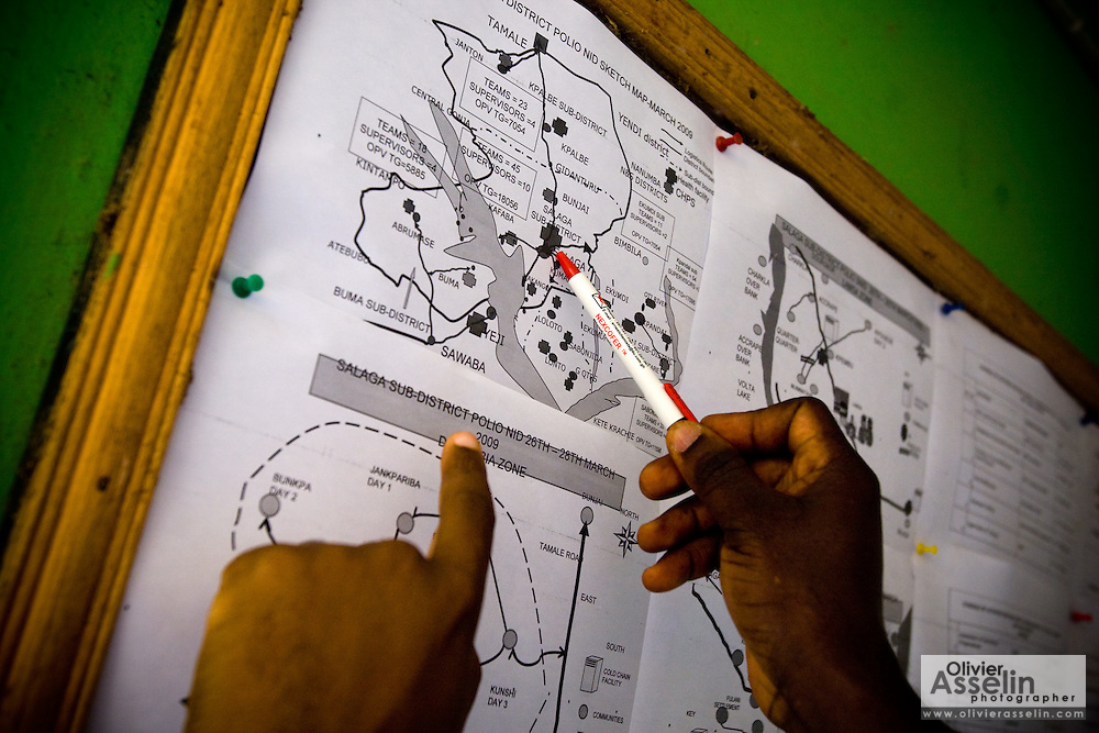 UNICEF staff and local health officials look at a map from a vaccination micro-plan at the health district directorate in Salaga, northern Ghana on Thursday March 26, 2009.