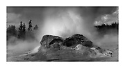 Castle geyser erupts on cold spring day, monochrome image, Yellowstone National Park