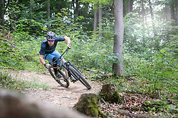 Mountain biker riding down hill on single track in forest, Bavaria, Germany