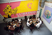 People eat lunch under a Cultural Revoliton themed mural in a Sichuan restaurant in Dashanzi. China's art scene is becoming popular among foreign art collectors pushing prices higher.