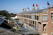 View of the buildings in the BedZED housing complex on Thursday, Sep. 6, 2007, in London, UK. BedZED or the Beddington Zero Energy Development, is an environmentally-friendly housing development near Wallington, England in the London Borough of Sutton. It was designed by the architect Bill Dunster who was looking for a more sustainable way of building housing in urban areas in partnership between the BioRegional Development Group and the Peabody Trust. There are 82 houses, 17 apartments and 1,405 square meters of work space were built between 2000. The project was shortlisted for the Stirling Prize in 2003. The project is designed to use only energy from renewable source generated on site. In addition to 777 square meters of solar panels, tree waste is used for heating and electricity. The houses face south to take advantage of solar gain, are triple glazed and have high thermal insulation while most rain water is collected and reused. Appliances are chosen to be water efficient and use recycled water wherever possible. Low impact building materials were selected from renewable or recycled sources and were all originating within a 35 mile radius of the site to minimize the energy required for transportation. Also, refuse collection facilities are designed to support recycling and the site encourage eco-friendly transport: electric and LPG cars have priority over petrol/diesel cars, and electricity is provided by parking spaces appositely built for charging electric cars.