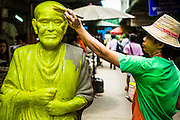 25 JUNE 2013 - BANGKOK, THAILAND:     A man puts a coat of primer paint on a statue of a revered monk in the Amulet Market in Bangkok. The market is adjacent to Wat Mahathat, between Maharat Road and the Chao Phraya River.    PHOTO BY JACK KURTZ