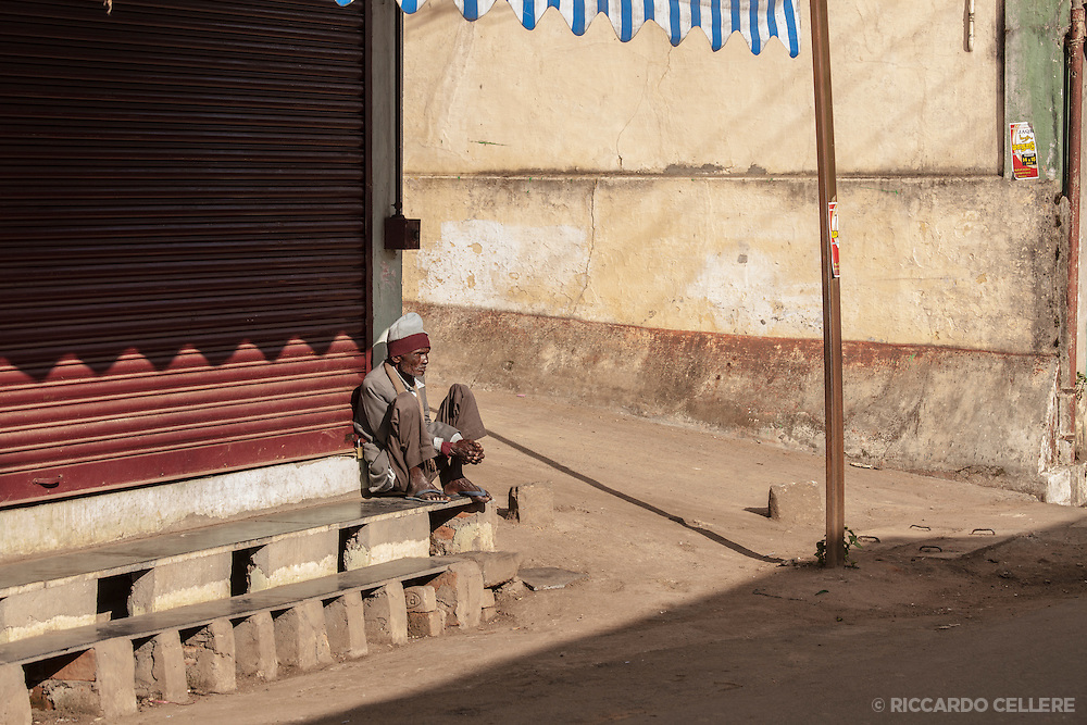 A man sits on a stoop in Ooty, India.