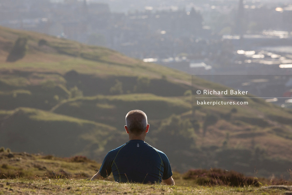 A man spends quiet, personal time overlooking the city of Edinburgh from Holyrood Park, on 26th June 2019, in Edinburgh, Scotland.