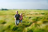 Boy and girl walking in tall grass prairie of Minnesota