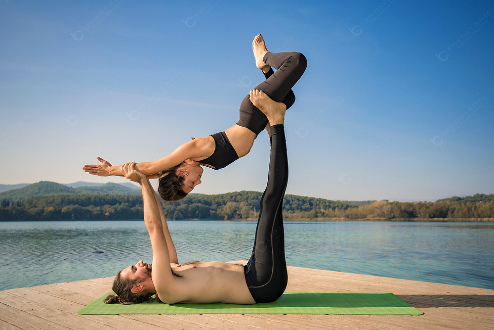 Couple practicing acroyoga in nature at beautiful lake Acroyoga Forward flying pose
