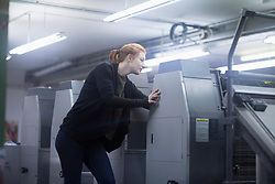 Worker standing by multiple printing machinery