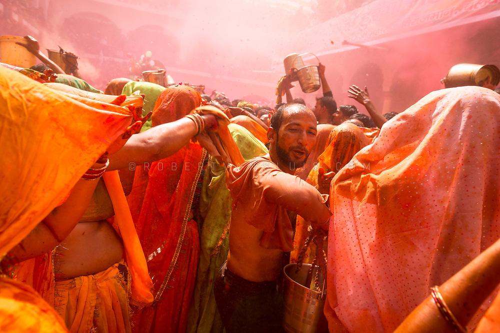 Women strip a man and hit him with wet clothes at the Huranga festival, Dauji temple, Baldeo, India. Photo © robertvansluis.com