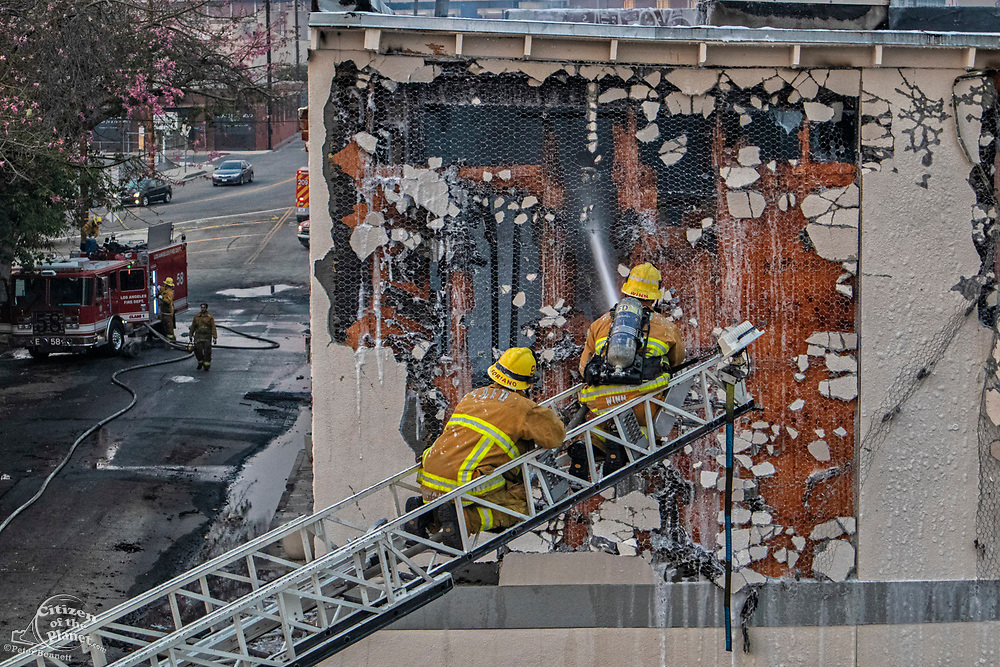 Fire fighters putting out warehosue fire in Downtown Los Angeles near 1st Street Bridge, California, USA