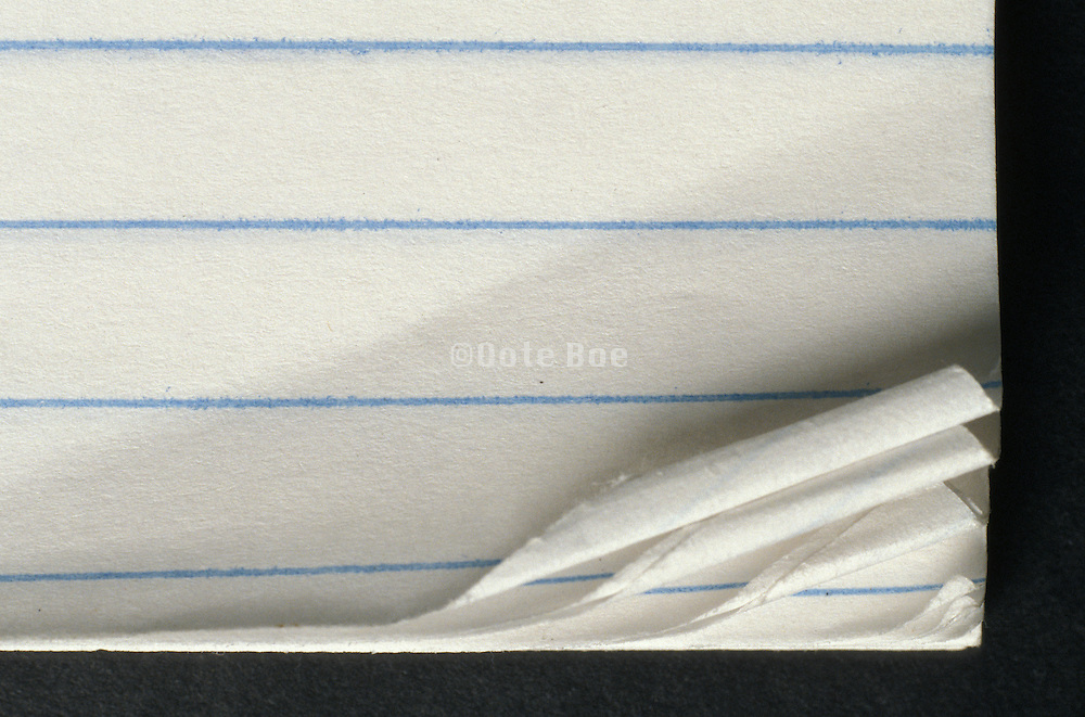 Detail of the curled edges of white note-book paper