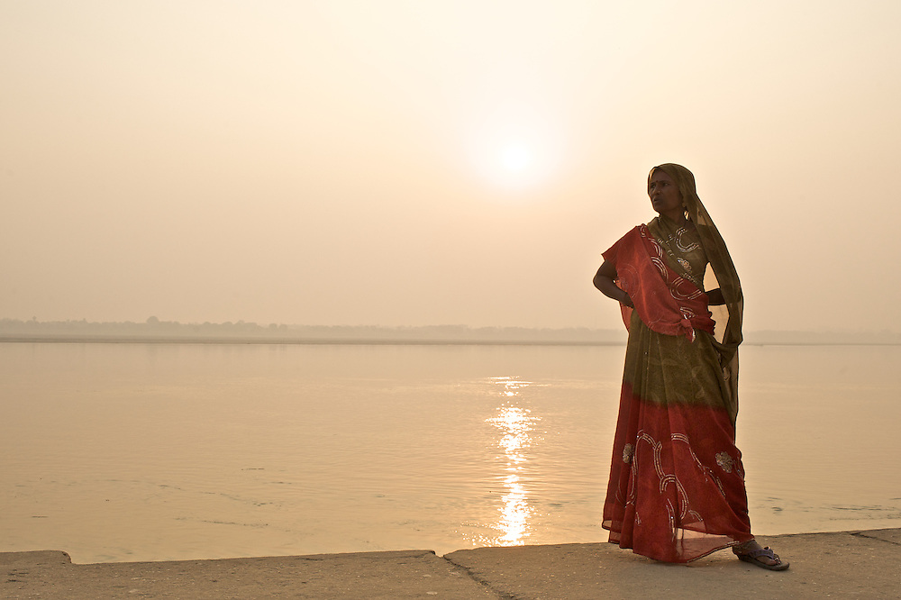 A woman stands along the Ganges River just after sunrise in Varanasi, India.