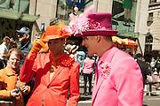 Two men dressed as dandies, one in orange, the other in magenta.